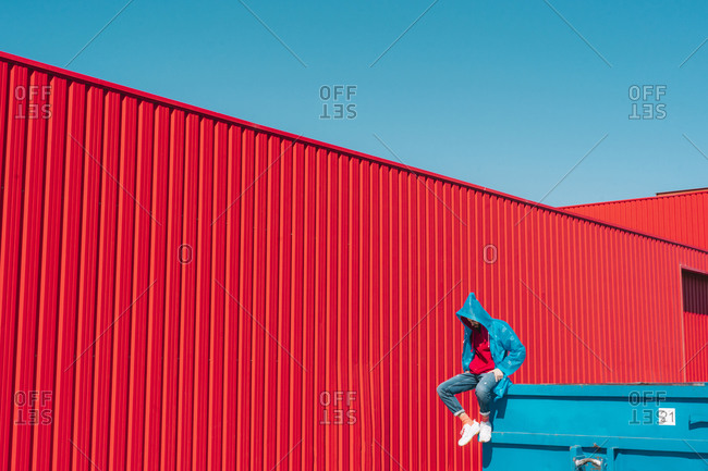 Young man wearing rain coat sitting on edge of blue container in front of red wall- looking down
