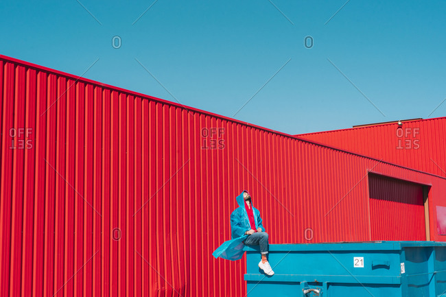 Young man wearing rain coat sitting on edge of blue container in front of red wall- looking up