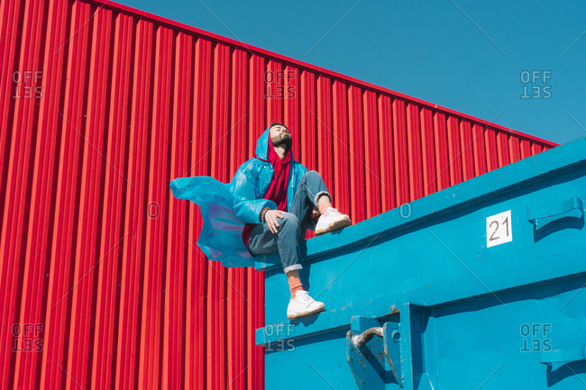 Young man wearing rain coat sitting on edge of blue container in front of red wall