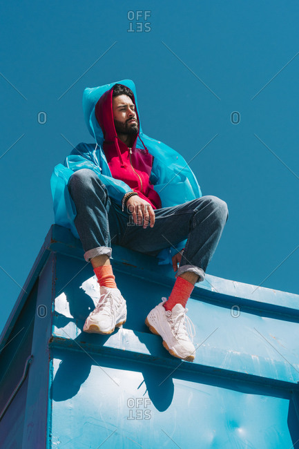 Young man sitting on edge of blue container- wearing rain coat