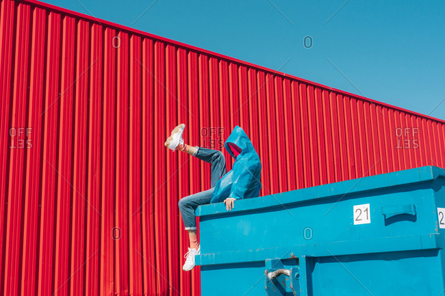 Young man wearing rain coat sitting on edge of blue container in front of red wall- raising leg