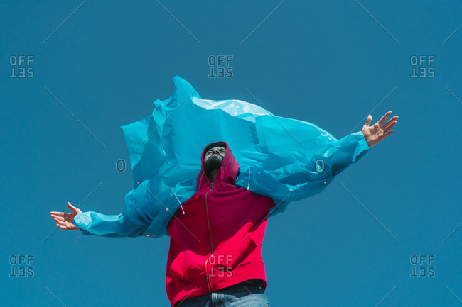Young man wearing plastic rain coat- stained in the wind with arms outstretched