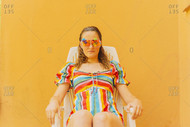 Portrait of woman wearing glasses with colorful pom poms covering her eyes relaxing on plastic chair