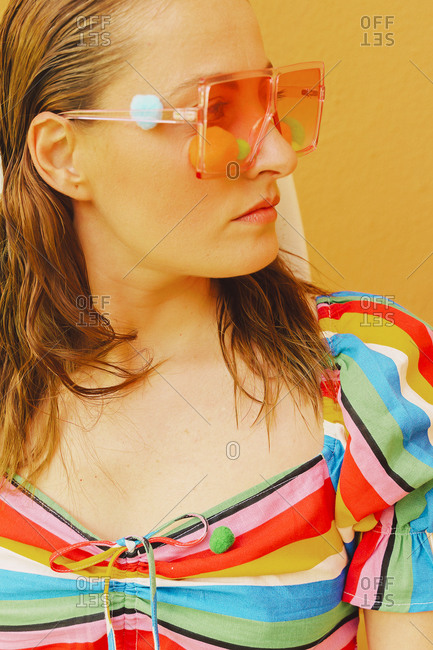 Portrait of woman wearing colored glasses with pom poms