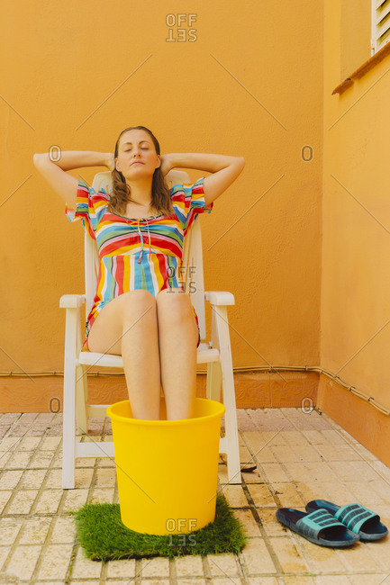Portrait of woman relaxing on plastic chair cooling her legs in bucket of water