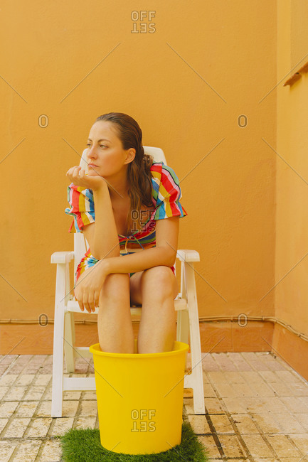 Portrait of serious woman relaxing on plastic chair cooling her legs in bucket of water