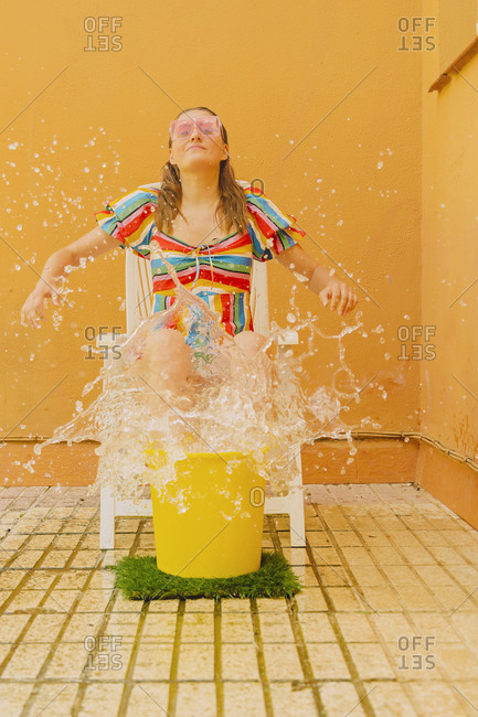 Portrait of woman sitting on plastic chair splashing with water
