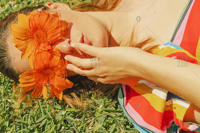 Portrait of woman lying on a meadow wearing glasses with orange flowers covering her eyes