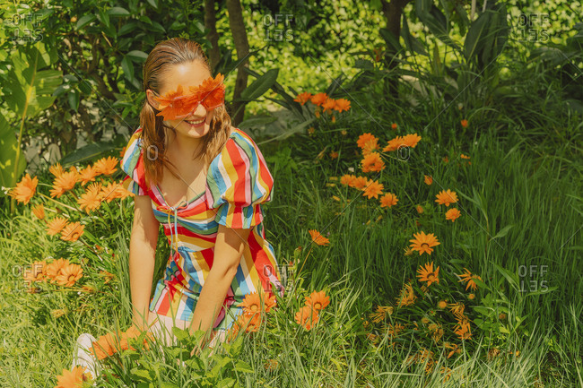 Portrait of happy woman in nature wearing glasses with orange flowers covering her eyes