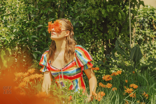 Woman in nature wearing glasses with orange flowers covering her eyes