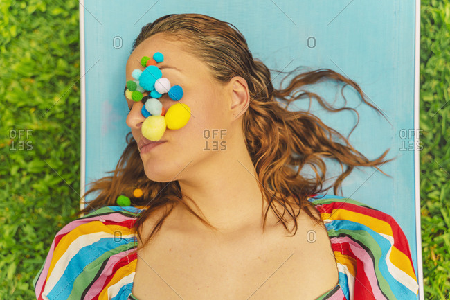 Portrait of woman with colorful pom poms on her face relaxing on sun lounger