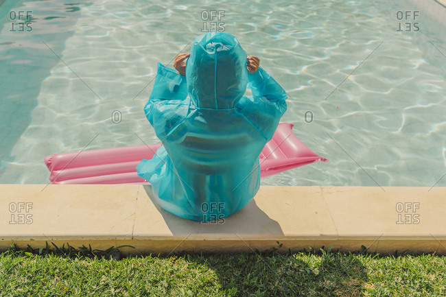 Back view of woman wearing blue rain coat sitting at poolside