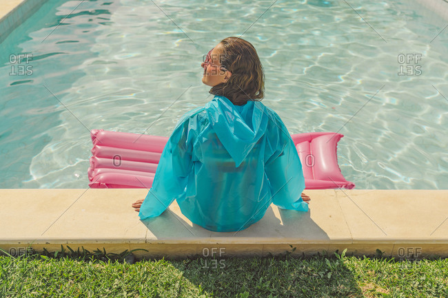 Back view of woman in blue rain coat sitting at poolside