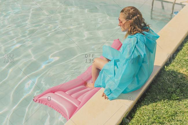 Woman in blue rain coat sitting at poolside