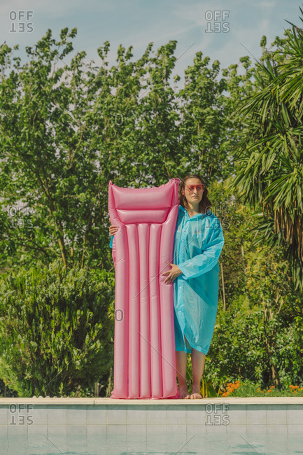 Woman in blue rain coat standing at poolside with pink airbed