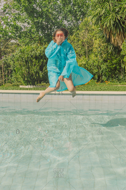 Woman in blue rain coat jumping into swimming pool