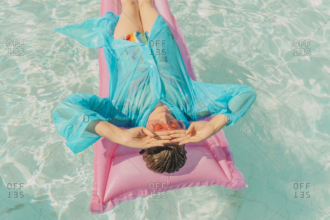Woman wearing blue rain coat relaxing on pink airbed in swimming pool
