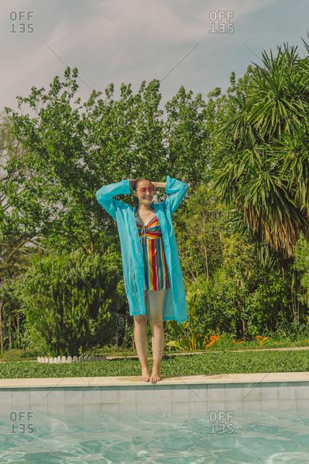 Smiling woman wearing blue rain coat standing at poolside
