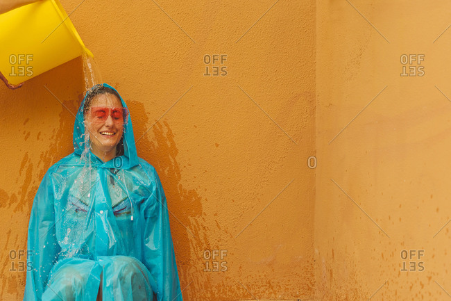 Portrait of woman wearing blue rain coat and colored sunglasses under flush