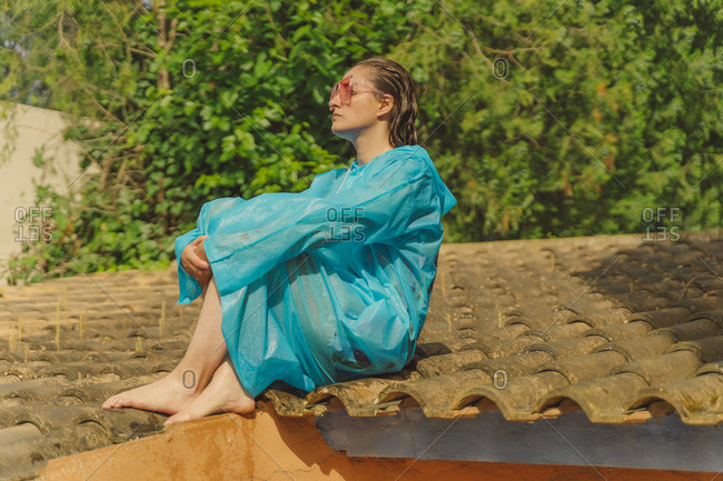 Woman wearing blue rain coat and colored sunglasses sitting barefoot on rooftop