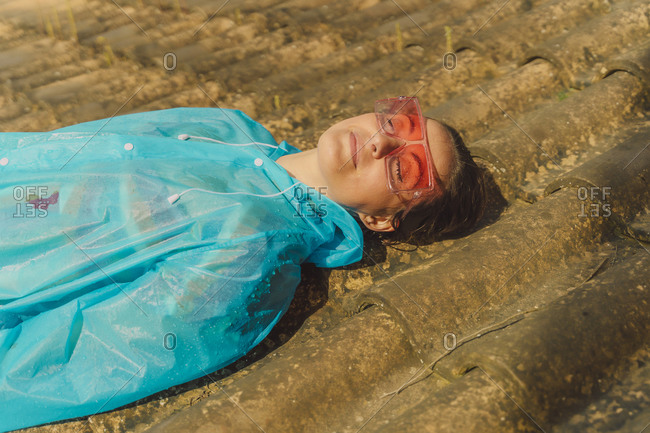 Portrait of woman wearing blue rain coat and colored sunglasses sunbathing on rooftop