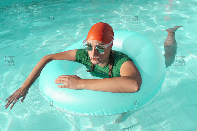 Portrait of woman with floating tire in pool wearing red swimming cap- green knit pullover and sunglasses