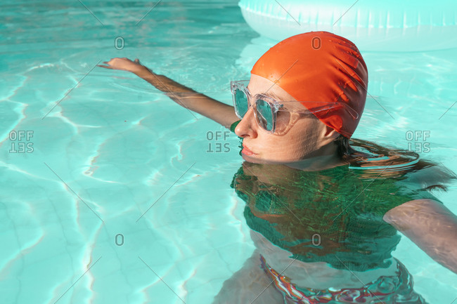 Portrait of woman in swimming pool wearing red swimming cap- green knit pullover and mirrored sunglasses