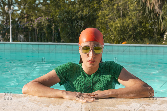 Portrait of woman leaning on poolside wearing red swimming cap- green knit pullover and mirrored sunglasses