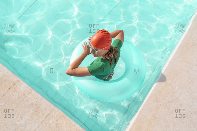 Woman with floating tire in swimming pool