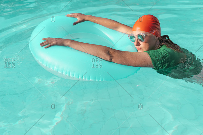 Portrait of woman wearing red swimming cap- green knit pullover and mirrored sunglasses in pool