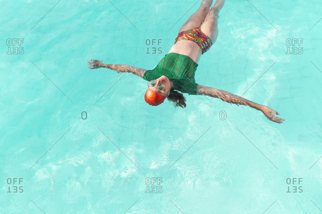 Woman floating on water in swimming pool