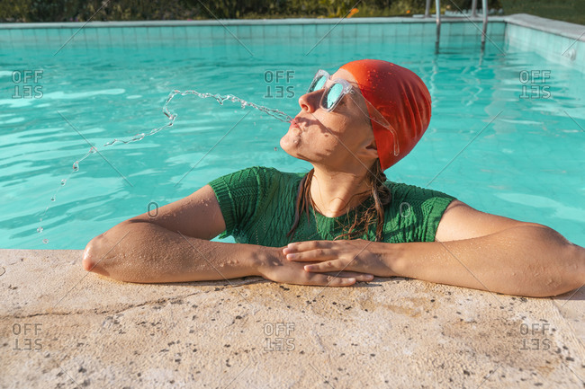 Portrait of woman leaning on poolside spitting water