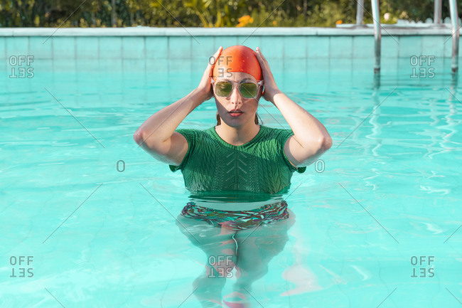 Portrait of woman in swimming pool wearing red swimming cap- green knit pullover and sunglasses