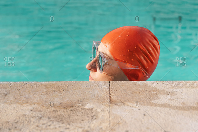 Woman at poolside wearing red swimming cap and sunglasses