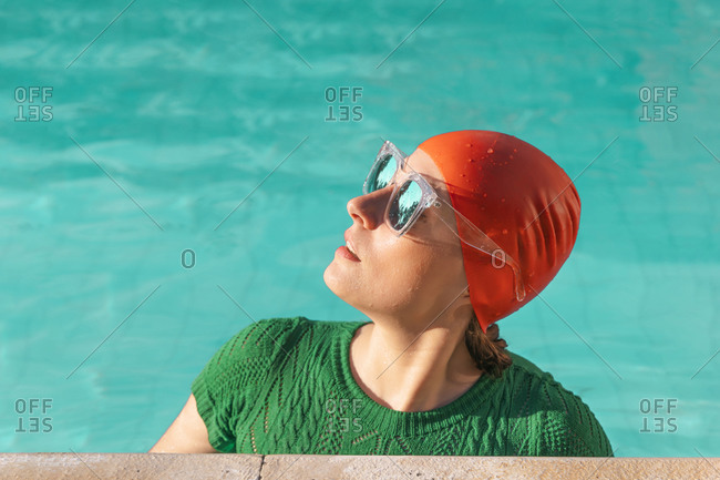 Portrait of woman at poolside wearing red swimming cap- green knit pullover and mirrored sunglasses