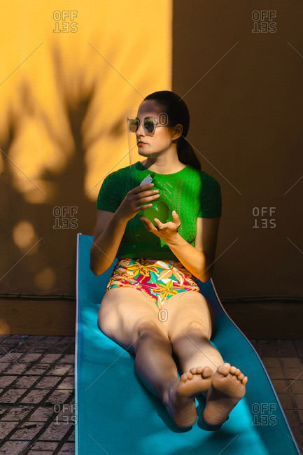Woman in colorful beachwear sitting in backyard- holding spray bottle