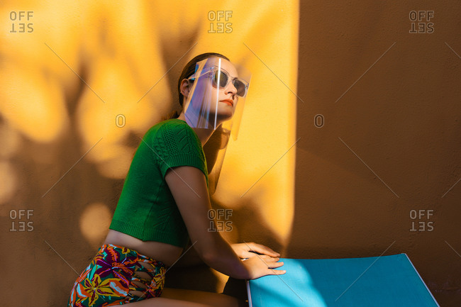 Woman in colorful backyard- wearing sunglasses under face shield