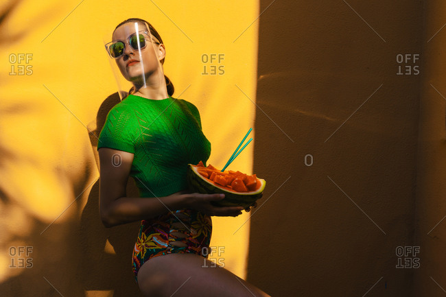 Woman in colorful backyard holding watermelon- wearing sunglasses under face shield