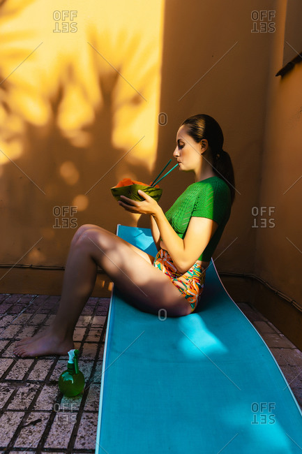 Woman sitting on sunbed in colorful backyard- holding watermelon- drinking from straw