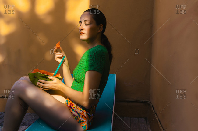 Woman sitting on sunbed in colorful backyard- holding watermelon