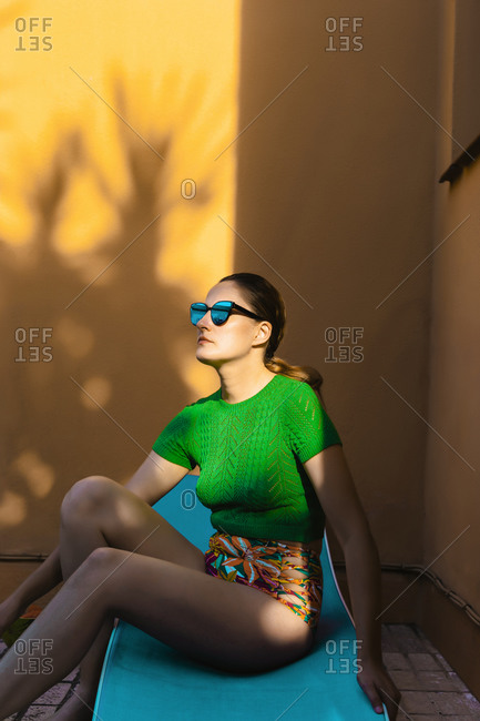 Woman with sunglasses sitting on sunbed in colorful backyard