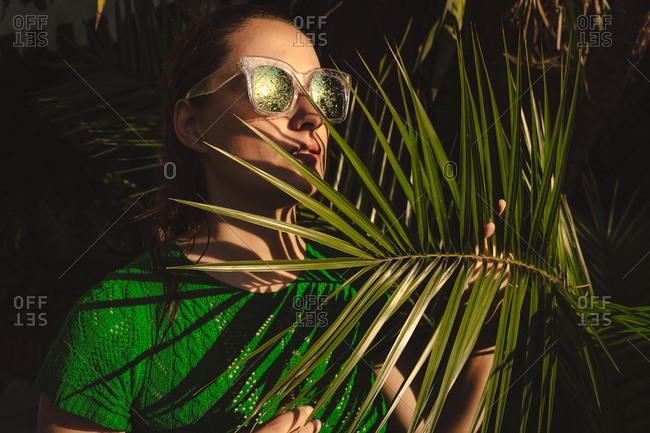 Woman with sunglasses hiding being palm leaves