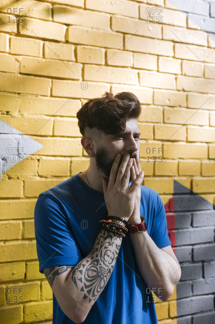 Young man with tattoo standing in front of yellow brick wall- covering mouth with his hands