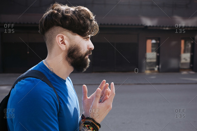 Young bearded man walking through the city