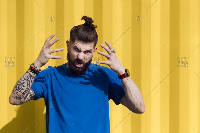 Angry young man with tattoo standing in front of yellow wall- gesturing