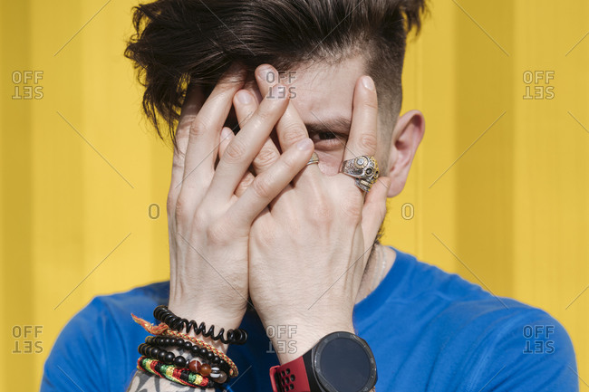 Young man standing in front of yellow wall- hiding face behind his hands