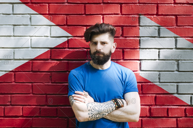 Young man with tattoo standing in front of red brick wall with arms crossed