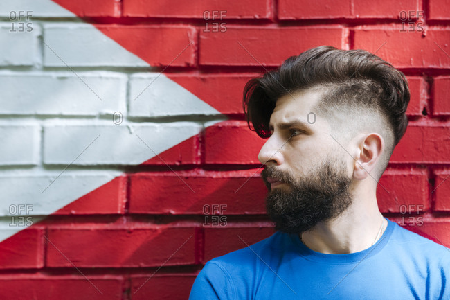 Young man with tattoo standing in front of red brick wall- portrait