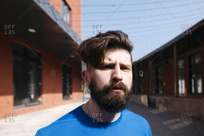 Portrait of young man walking in the city- looking serious