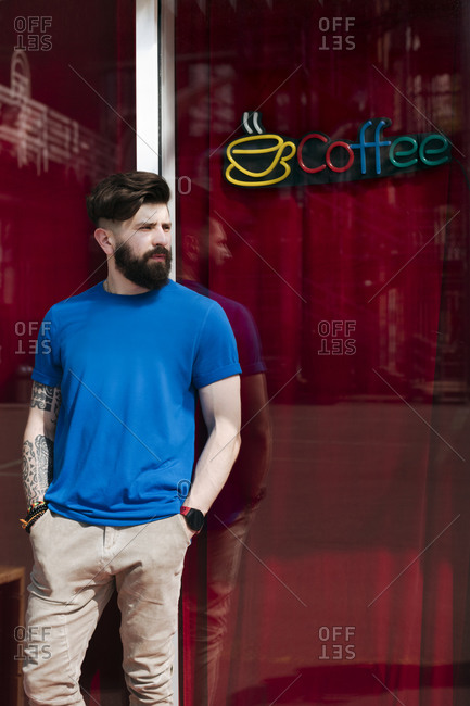 Young man leaning on windowpane of coffee shop